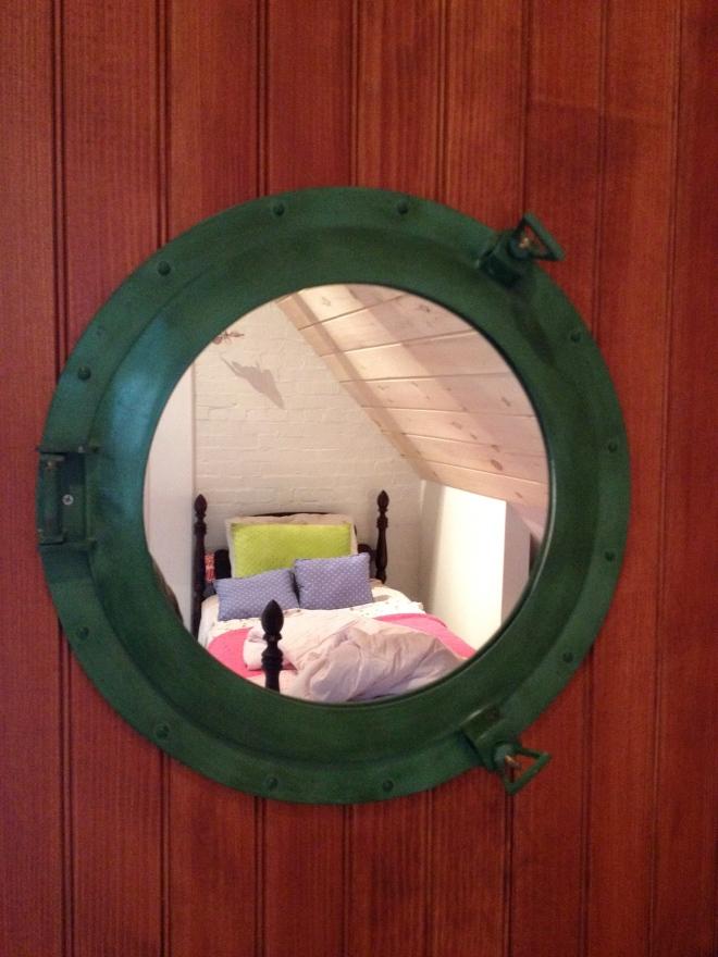 Sliding barn door with a port hole mirror